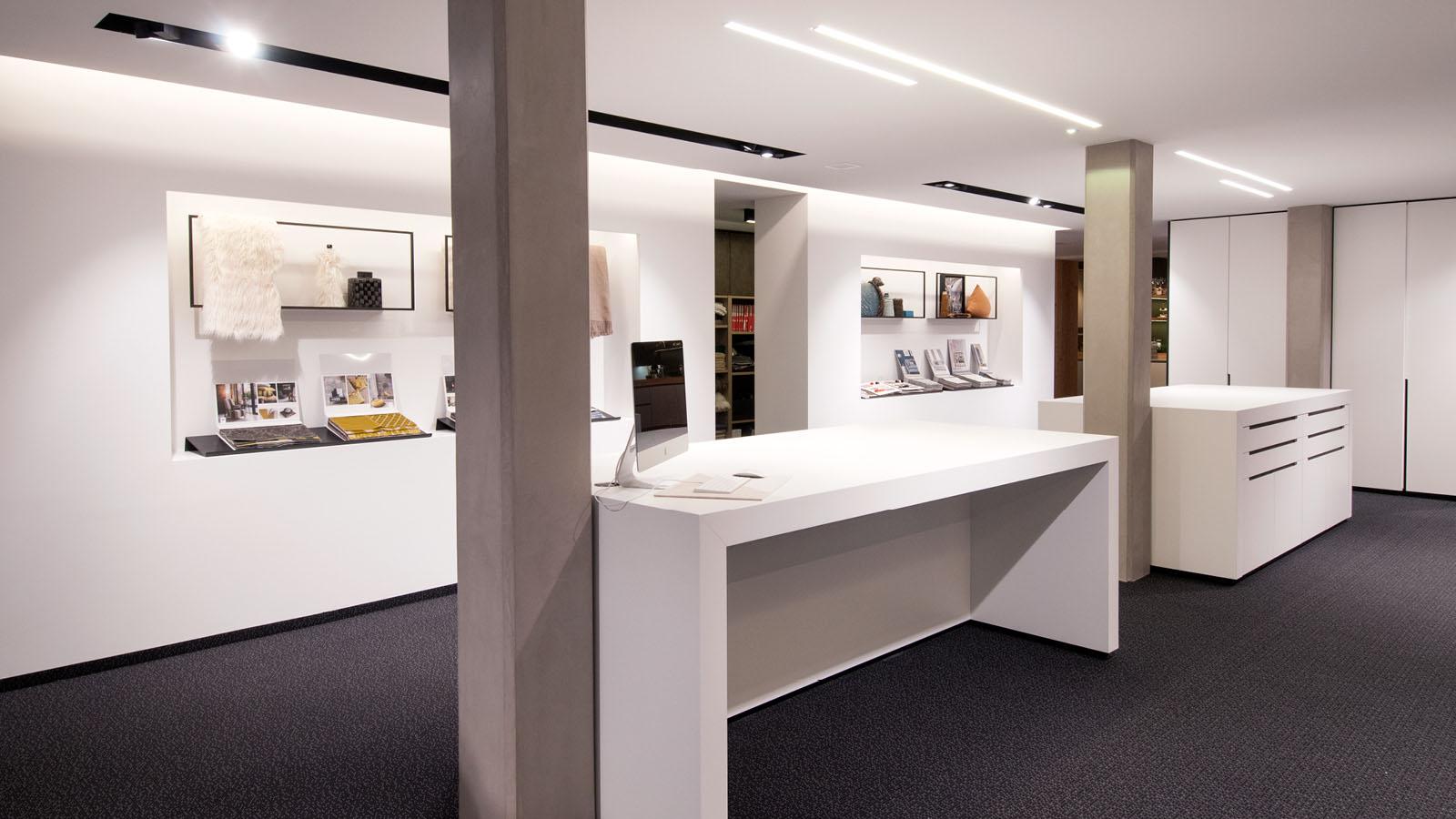 Planungsbüro mit weißen Tischen und Textilmustern an der Wand