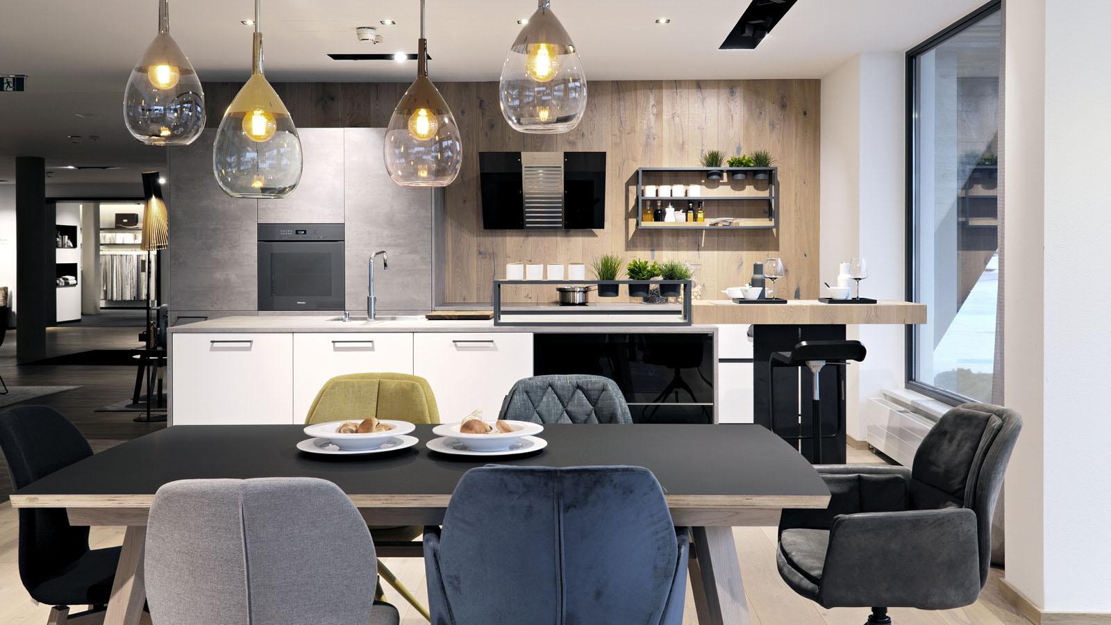 Bunte Ledersessel um einen Tisch, Küche mit Frühstücksbar im Hintergrund