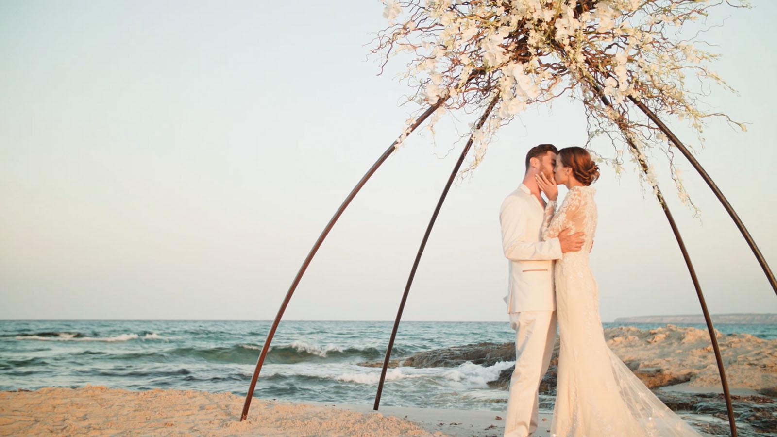 Brautpaar küsst sich unter einem geschmückten Bogen am Strand