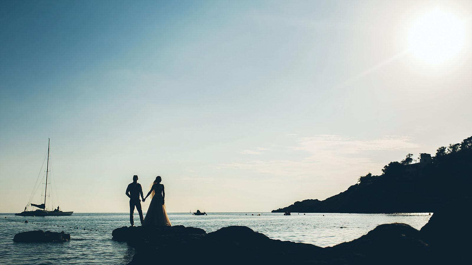 Brautpaar steht auf Felsen mit Blick auf das Meer und die untergehende Sonne