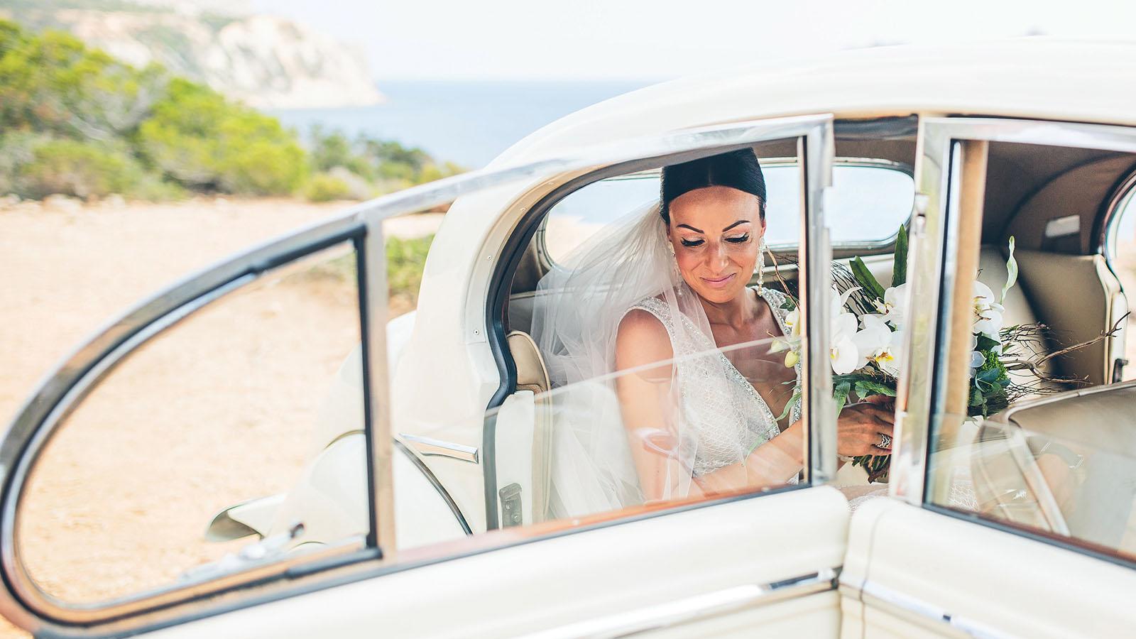 Braut mit Schleier und Blumenstrauß steigt aus einem weißem Auto mit