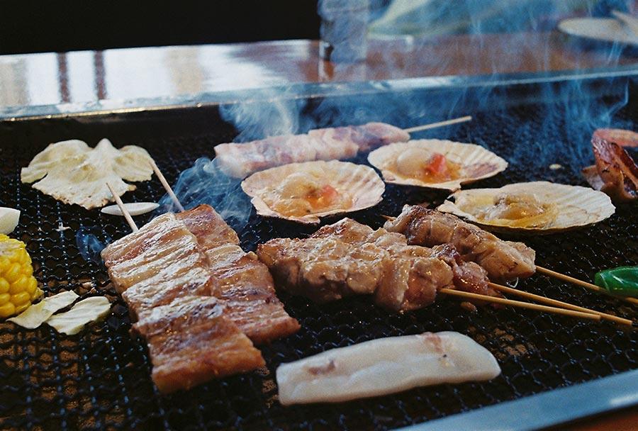 Fischspieße und Muscheln auf dem Grill